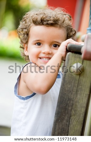 A cute young kid playing outside at the park - stock photo
