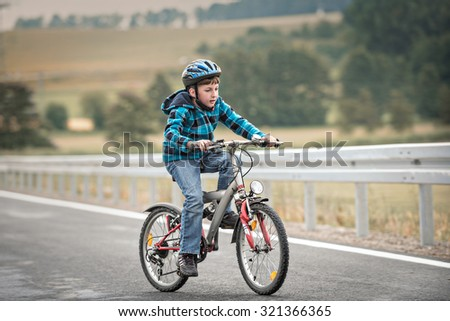 A cute young kid riding a bicycle with a helmet on. - stock photo