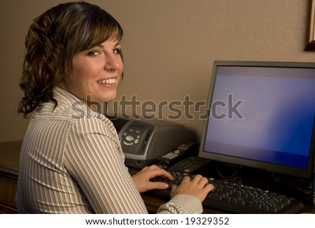 A cute young professional working on the computer - stock photo