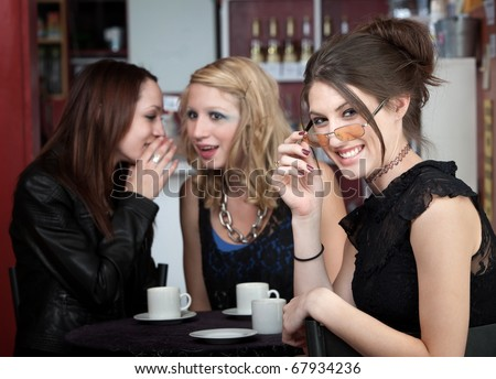 A cute, young teenage girl smiling while her friends share a secret