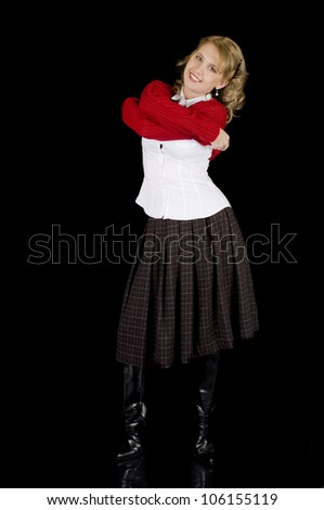 A cute young woman is removing her sweater.  Isolated on black - stock photo