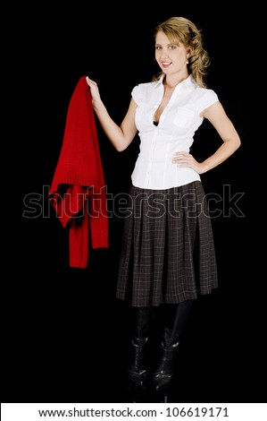 A cute young woman is removing her sweater.  Isolated on Black. - stock photo