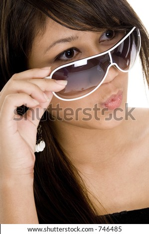 A cute young woman looks over the top of funky sunglasses and whistles