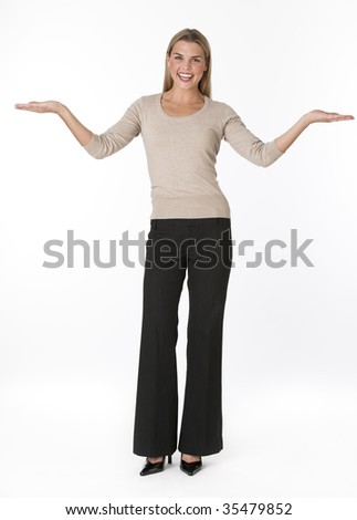 A cute young woman posing with outstretched arms.  She is smiling directly at the camera.  Vertically framed shot. - stock photo