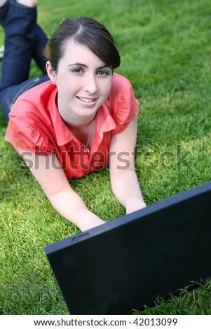 A cute young woman student on computer on grass in the park - stock photo