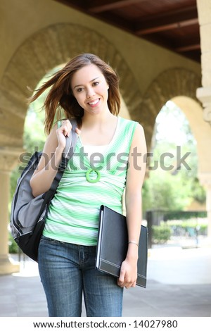 A cute young woman walking to class on university campus - stock photo