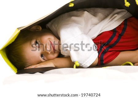 A cute 3yr old playing with a shopping bag. - stock photo