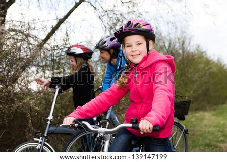 A cycling family in front of rural landscape - stock photo