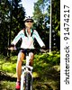 A cycling woman in front of forest - stock photo