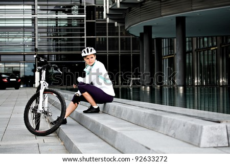 A cycling woman in front of urban background - stock photo