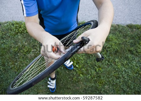 A cyclist changing his bike tire. - stock photo
