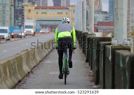 A cyclist commutes on his bike in a city/Cyclist Commuting in the City/A cyclist commutes on his bike in a city.