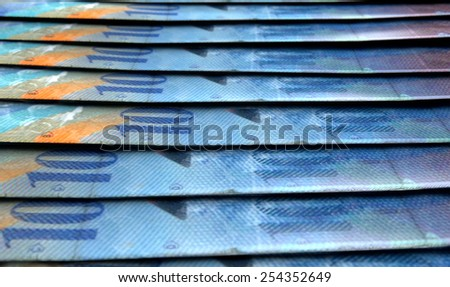 A 3D rendering of a macro close-up view showing the detail of swiss franc banknotes laid out and overlapping in a staggered row - stock photo