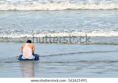 A dad and his boy sitting on the shore of the beach. - stock photo