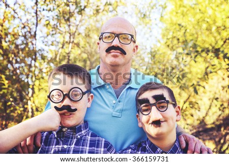 a dad with his sons all acting goofy wearing mustaches during a summer day toned with a retro vintage instagram effect app or action - stock photo
