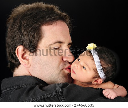 A Daddy holding and kissing his newborn daughter.  On a black background. - stock photo