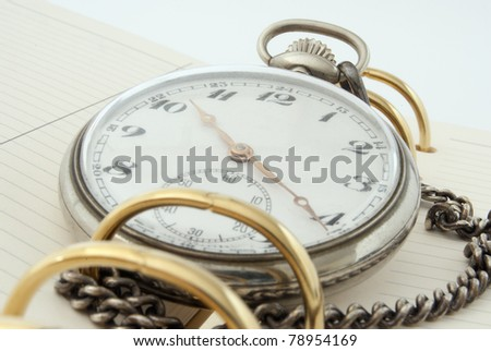 A daily planner with a pocket watch - stock photo