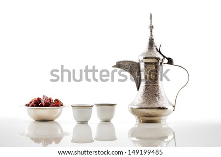 A dallah is a metal pot with a long spout designed specifically for making Arabic coffee, seen here with a bowl of dried dates and two cups - stock photo