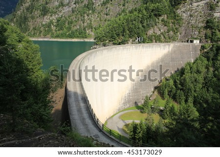 A dam holds a green reservoir in a valley in the canton Tessin, Switzerland