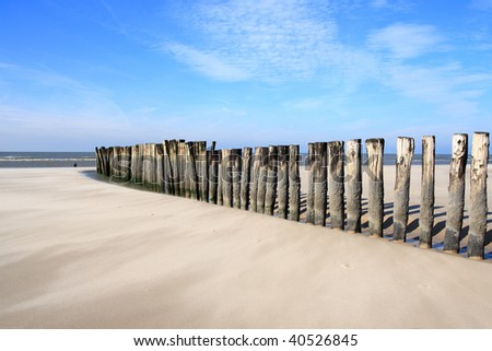 a dam of wooden poles, on the beach