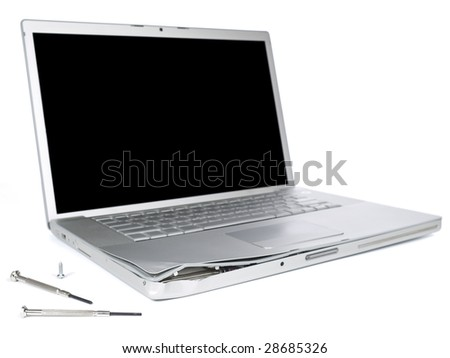 A damage laptop computer is about to be fixed with a pair of clockwork screwdrivers. Isolated on white. - stock photo