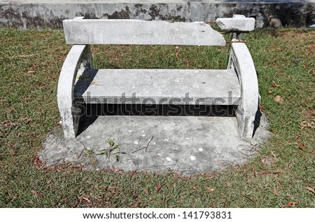 A damaged concrete bench in a park.