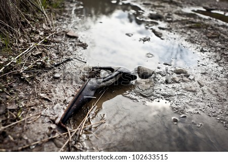 A damaged high-heeled shoe lies in the mud, a broken heel. - stock photo