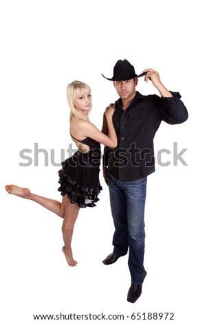 A dancer hanging on to her cowboy in his black hat. - stock photo