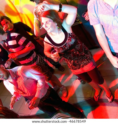 A dancing woman in a nightclub surrounded by a group of people. - stock photo