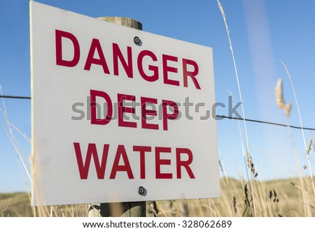 "A ""danger deep water sign"" fixed to a fence around the edge of a lake - stock photo"