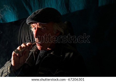 A dangerous looking man with an evil expression on his face is sitting in a dark room looking at viewer smoking pipe. - stock photo