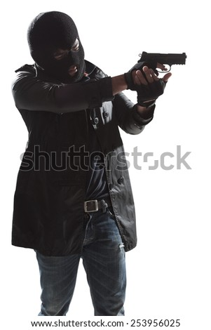 A dangerous man in the dark holding gun standing isolated on white background with clipping path - stock photo
