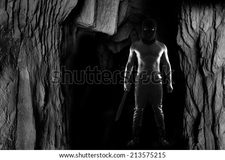 A dangerous man wearing a balaclava camouflage and holding knife standing in the dark cave - stock photo