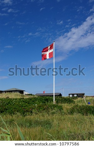 A danish flag in typical danish sommerhouse surroundings - stock photo