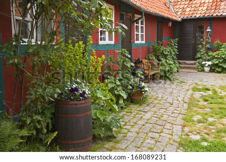 A danish townhouse with lush inner garden and garden path. - stock photo