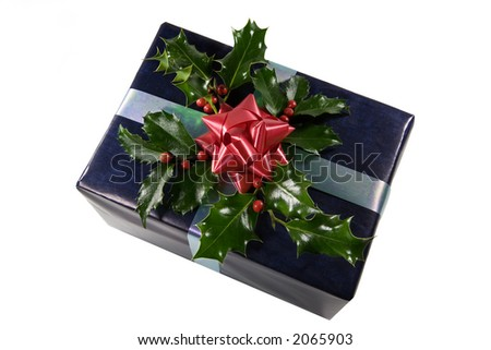 a dark blue gift with a red bow decorated with holly berries on white - stock photo