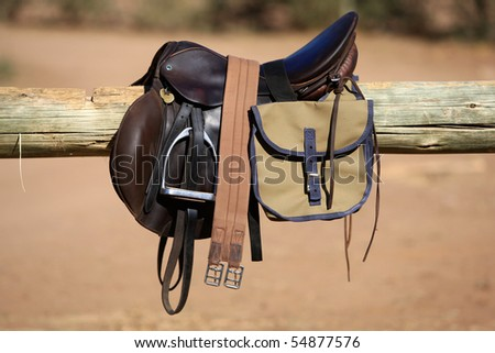 A dark brown saddle resting on a pole in full sunlight - stock photo