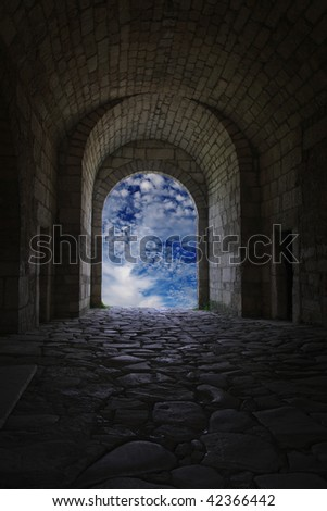 A dark corridor with a arch opening to a beautiful cloudy sky