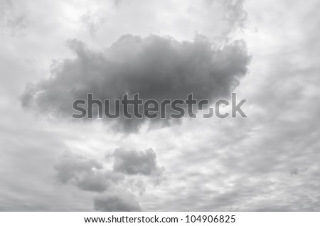 A dark grey cloud in a grey sky. - stock photo