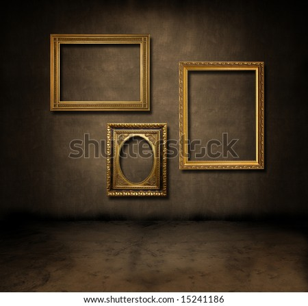 A dark, grungy room with gold frames on the wall - stock photo