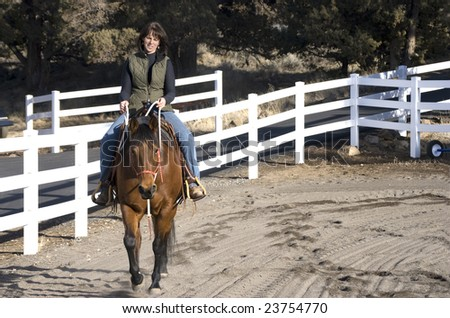 A dark haired attractive woman riding a beautiful bay quarter horse - stock photo