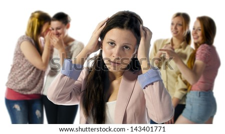 A dark haired girl is desperate and holds his hands to his head in the background are out of focus four girls who laugh at them. - stock photo