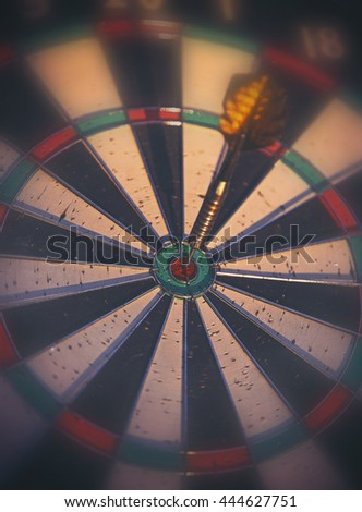 a dark moody image of a dartboard with a dart in the center bulls eye circle toned with a retro vintage instagram filter app or action effect and a blurred vignette