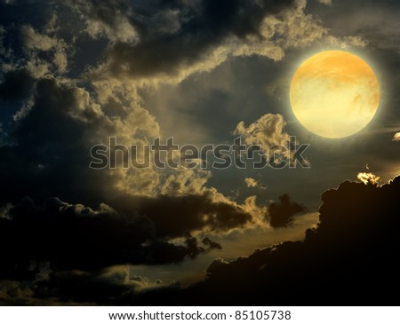 A dark night brings a bright, amber moon alive with puffy hazy - stock photo