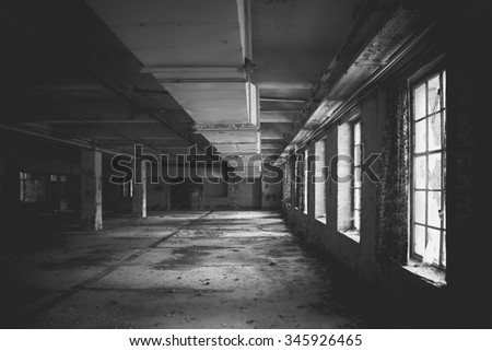 A dark scary abandoned factory floor in black and white