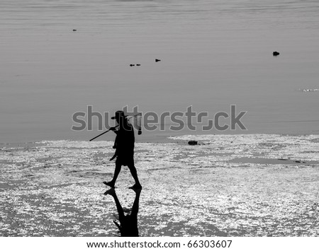 A dark silhouette image of an unrecognizable fisherman walking along a beach. - stock photo