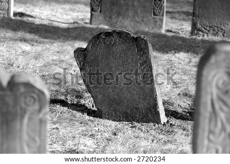 a dark stone stands out in this scene of ancient grave stones in black and white in bright sun light on a beautiful winter's day - stock photo