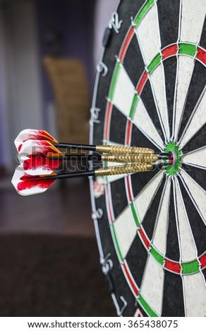 A dartboard close-up with three bullseye hits. - stock photo