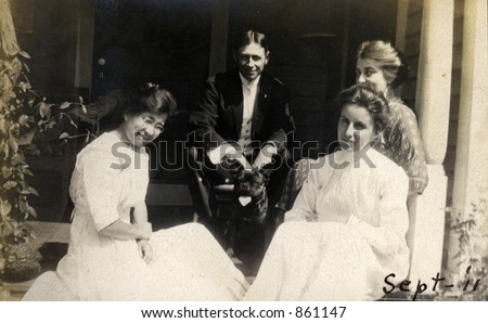 A dashing young man enjoys the attention of several young ladies.  Original Circa 1911 print has scratches, artifacts, fading and solarization qualities. - stock photo