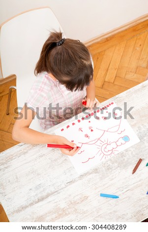 A daughter drawing at the table at home.